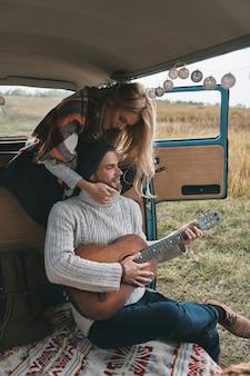 Musik spielen, die sie mag. hübscher junger mann, der gitarre für seine schöne freundin spielt, während er im mini-van im retro-stil sitzt