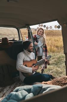 Musik überall hin mitnehmen. hübscher junger mann, der gitarre für seine schöne freundin spielt, während er im mini-van im retro-stil sitzt