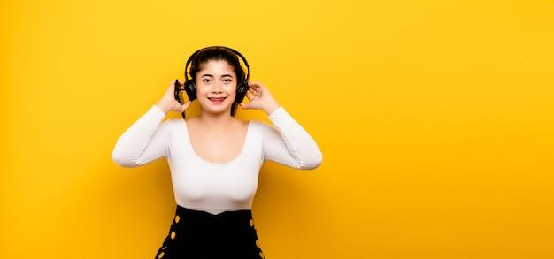 Musik und entspannung asiatische frau, die ein telefon verwendet, um musik zu hören asiatische frau, die ein smartphone auf gelbem hintergrund mit freiem speicherplatz verwendet