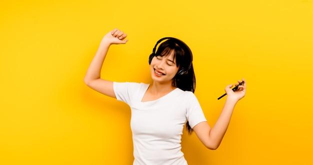 Musik- und entspannungskonzept schöne asiatische frau in kopfhörern, die musik hört und auf gelbem hintergrund glücklich im leben tanzt