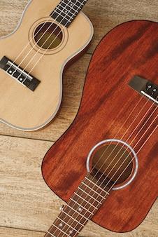 Musik von herzen. vertikale draufsicht auf die nahe beieinander liegenden akustik- und ukulele-gitarren auf dem holzboden. musikkonzept. musikinstrumente