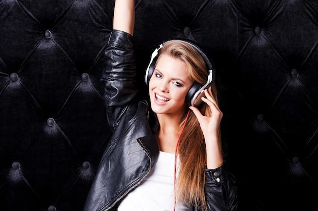 Musikalisch macht spaß. schöne junge frau mit make-up und kopfhörern posiert vor schwarzem hintergrund