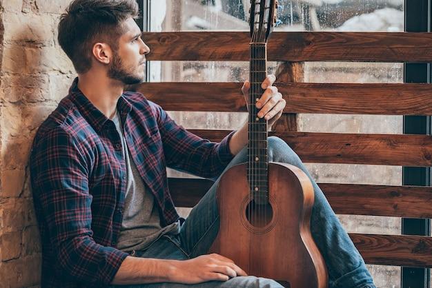 Musikalische inspirationen. seitenansicht eines gutaussehenden jungen mannes, der gitarre hält und durch das fenster schaut, während er auf der fensterbank sitzt