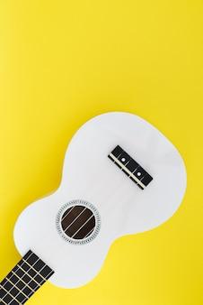Musikalisches konzept. weiße hawaiianische gitarre auf gelbem grund. ukulele auf einem hellen hintergrund