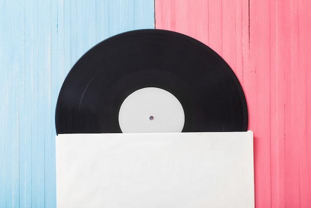 Musikaufzeichnungen auf rosa und blauem hölzernem hintergrund. retro musikkonzept