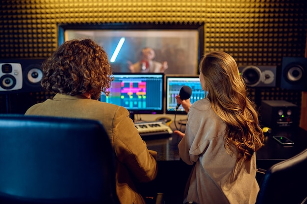 Musiker am mischpult, aufnahmestudio im hintergrund. synthesizer und audiomixer, musikerarbeitsplatz, kreativer prozess, songaufnahme