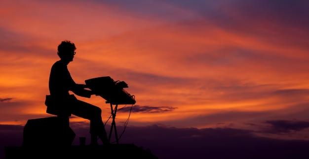 Musiker, der das elektrische klavier auf dem sonnenuntergang spielt