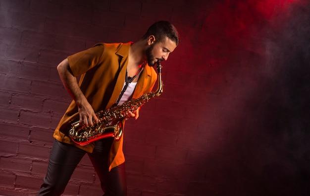 Musiker, der das saxophon im nebel mit kopierraum spielt