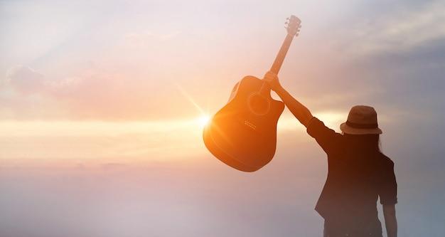 Musiker, der in der hand akustikgitarre auf sonnenuntergang hält