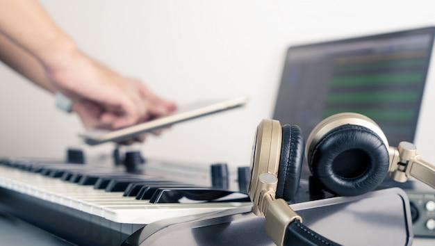 Musiker, der tabelle verwendet, um arbeitsstudioanwendung des musikstudios zu steuern