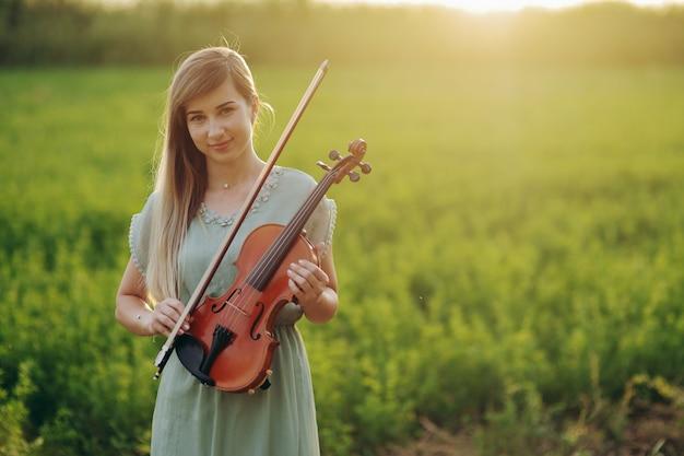 Musiker-geigerin, die geige in ihren händen im sonnenuntergangslicht hält