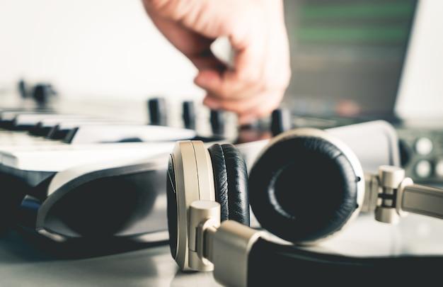 Musiker mischt und justiert spur auf portable computer music studio nach hause eingerichtet