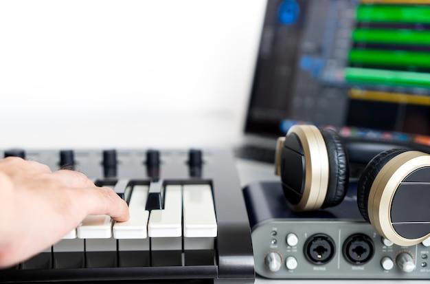 Musiker nimmt tragbares computer-musik-studio auf, das nach hause aufgestellt wird