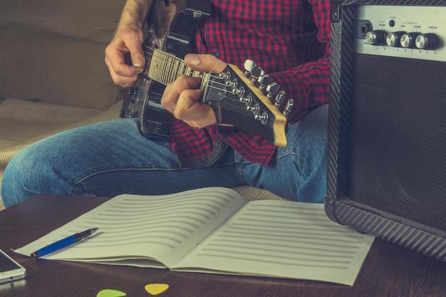 Musiker sitzt auf der couch und spielt die e-gitarre. vor ihm die notizen und eine guita