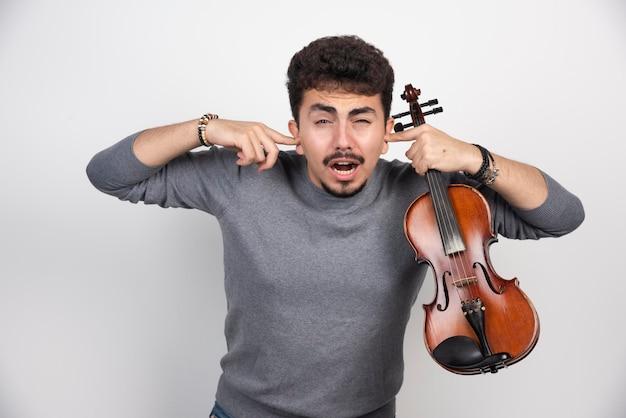 Musiker spielt geige und weigert sich, die kritiker zu hören.