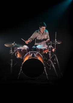 Musiker spielt schlagzeug, schwarzer hintergrund und schönes weiches licht, emotionales spiel, musikkonzept