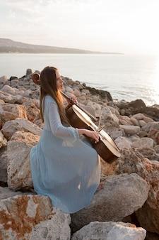 Musikerin, die draußen cello bei sonnenuntergang spielt