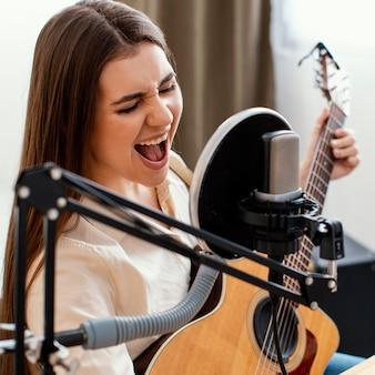 Musikerin singt und nimmt lied mit akustischer gitarre auf