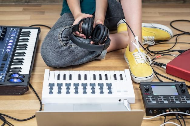 Musikerin sitzt in einem heimstudio mit modernen elektronischen instrumenten. junge frau, die moderne indie-musik auf synthesizer und digitalen controllern produziert