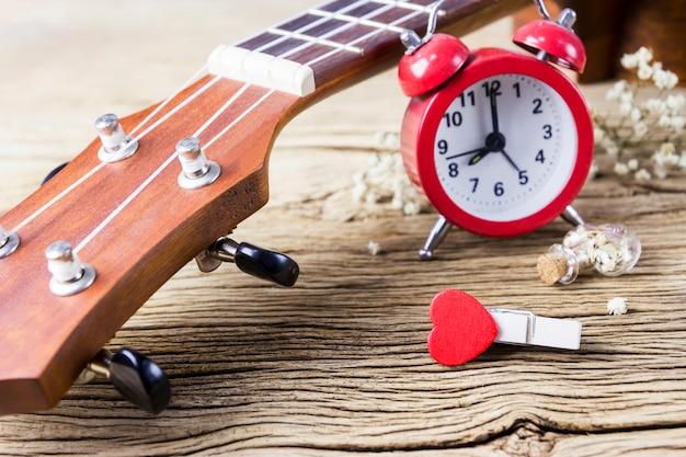 Musikfreundkonzept der ukulele und rotes herz kleidet klammer auf altem holz