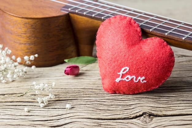 Musikfreundkonzept des ukulele und rotes herz auf altem holz