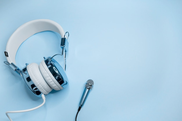 Musikhintergrund mit blauen kopfhörern und mikrofon.