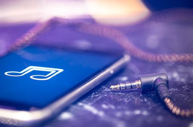 Musikhintergrund mit einem musikwiedergabesymbol auf dem telefon und den kopfhörern.