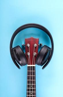 Musikhintergrund: ukulele und kopfhörer über blau