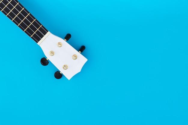 Musikinstrument ukulele auf einem blauen hintergrund und einem platz für text. griffin der hawaiianischen gitarre. musikalisches konzept