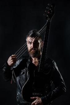 Musikinstrumente rocken bärtiger mann mit e-gitarrengitarrist in schwarzen lederjackenständern