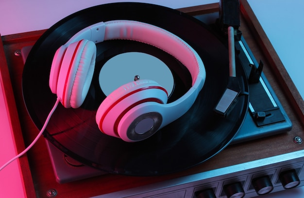 Musikkonzept im retro-stil. klassische kopfhörer, schallplatte mit rosa-blauem neonlicht. popkultur. 80er jahre.