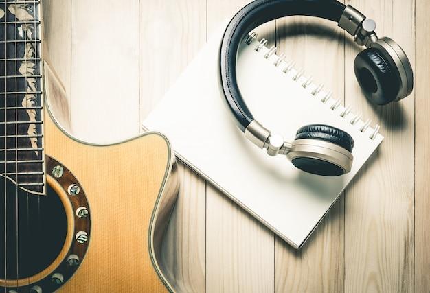 Musikkopfhörer mit gitarre auf hölzerner tablette.