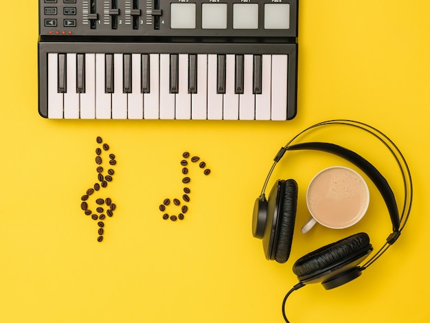 Musikmischer, kaffeebohnennoten und kopfhörer auf gelbem hintergrund. das konzept des musikschreibens. ausrüstung zum aufnehmen von musiktiteln. der blick von oben. flach liegen.
