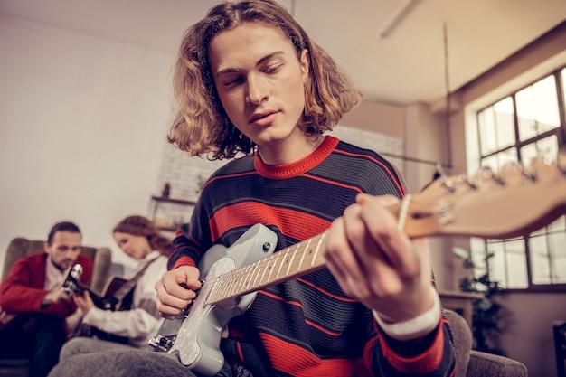Musikstudent. nahaufnahme eines talentierten musikstudenten, der einen roten und blauen pullover trägt, der gitarre spielt?