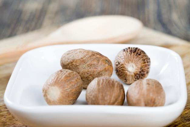 Muskatnuss auf einem alten holztisch in der küche verstreut, wird aromatische muskatnuss beim kochen während der zubereitung von fleisch und anderen gerichten verwendet, nützliche gewürze nahaufnahme