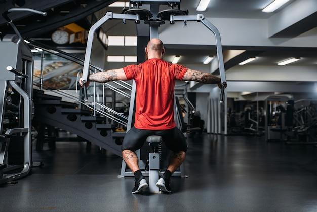Muskelathlet auf übungsmaschine im fitnessstudio, rückansicht.