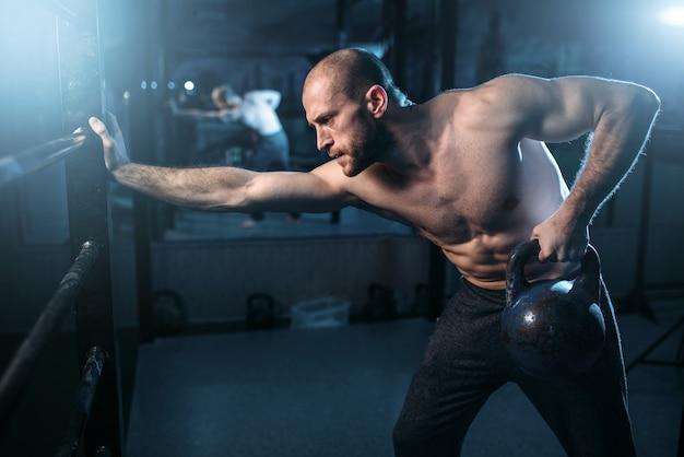 Muskelathletentraining, mann, der kettlebell anhebt. starkes sporttraining mit gewicht