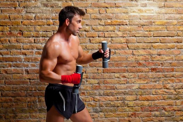 Muskelboxer-mann mit faustverband und gewichten