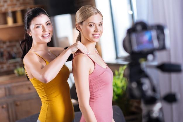 Muskelentspannung. schöne positive junge frau, die hinter ihrer freundin steht und massage tut, während sie ihre muskeln entspannt