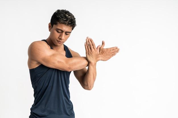 Muskelmann, der sportswear steht, steht zur seite und streckt die hand