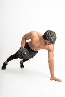 Muskelmann ohne kleidung macht übungen mit einer hantel in der hand