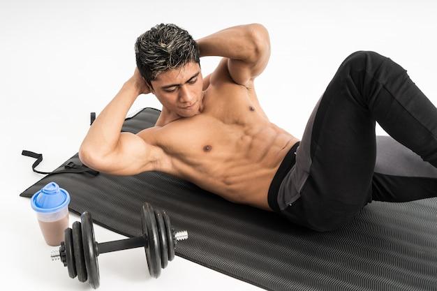 Muskelmann ohne kleidung macht übungen mit einer matte neben der flasche und der hantel