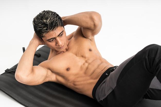 Muskelmann ohne kleidung macht übungen mit einer matte