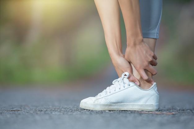 Muskelschmerzen der frau während des lauftrainings