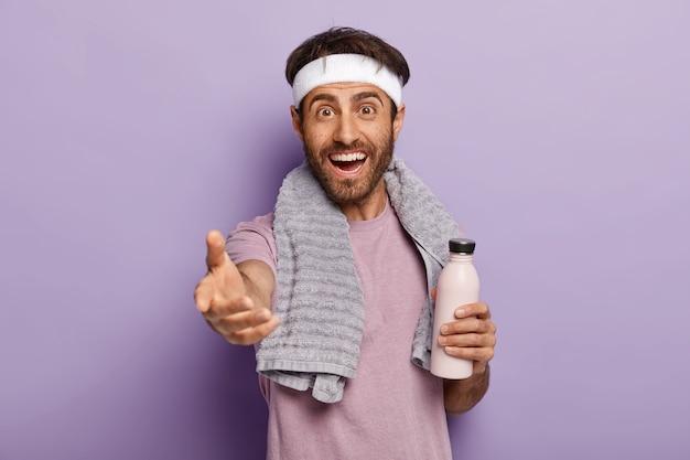 Muskelsportler trinkt wasser aus der flasche