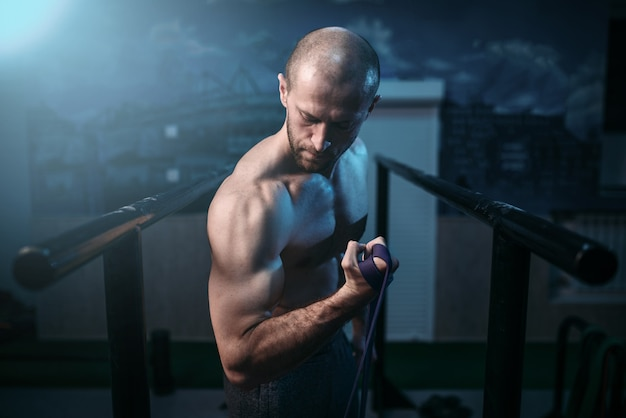 Muskelsportlerübungen mit elastischem gummiband.