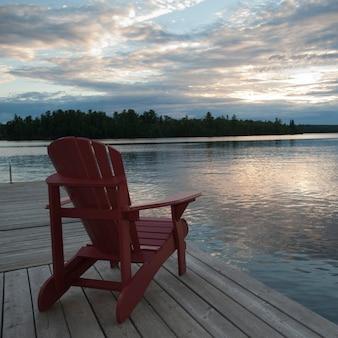 Muskoka-stuhl auf dock am see des holzes, ontario