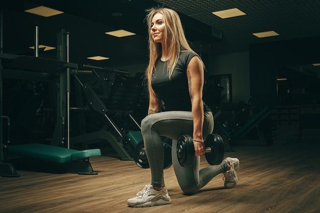 Muskulöse attraktive frau im fitnessstudio, das hanteln hebt