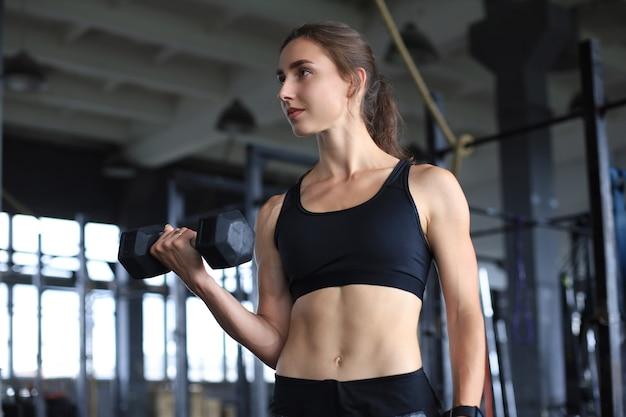 Muskulöse fitte frau, die muskeln im fitnessstudio trainiert.