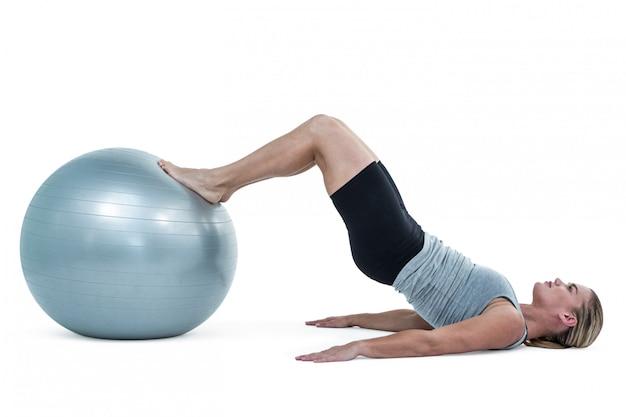 Muskulöse frau, die auf boden mit den beinen auf übungsball liegt